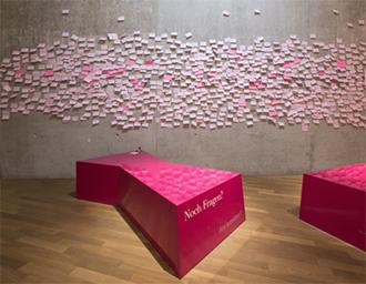 Eine Wand mit pinken Post-its beklebt, davor zwei liegende Vitrinen mit der Aufschrift »Noch Fragen?«