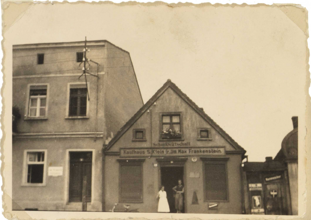 """The picture shows a house. Above the entrance door there is a sign with the inscription """"Schankwirtschaft // Kaufhaus S. Klein jr. Inh. Max Frankenstein"""". In the entrance door there is a woman in a light dress (Martha Frankenstein) and a young man."""