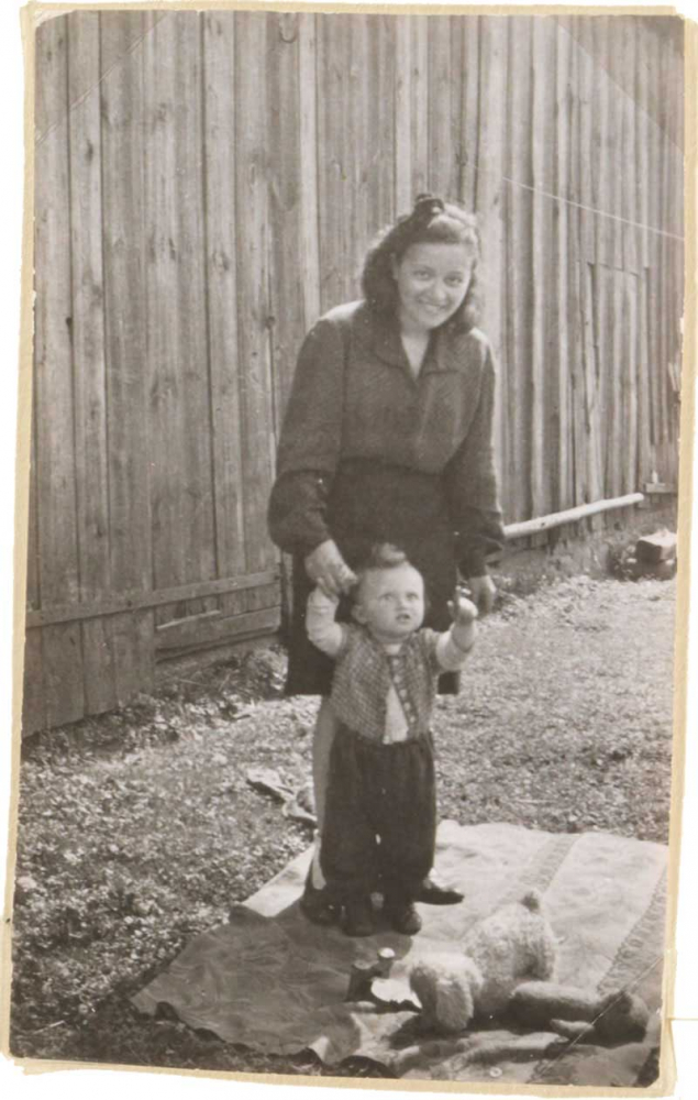 The photo shows a toddler held by a woman's hands (black and white photograph).
