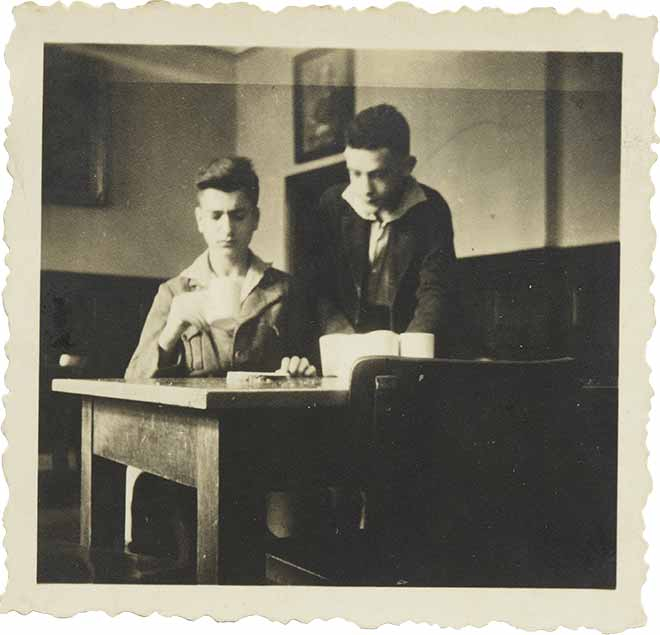 Two boys at a table, one sitting with a cup, one standing diagonally behind him (black-and-white photo)
