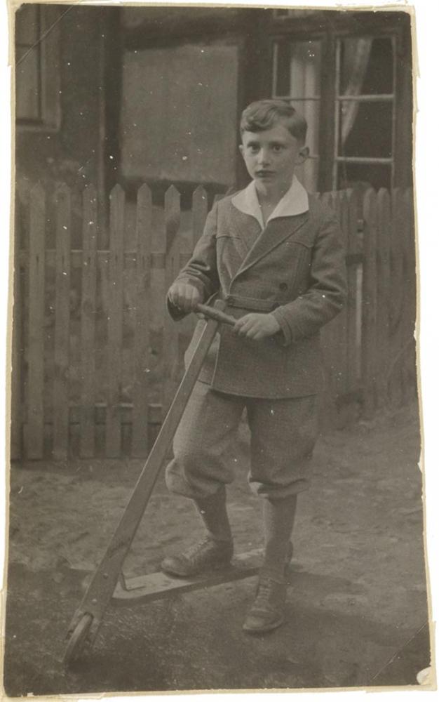 Walter Frankenstein's photograph as a child in fine clothing and standing in front of a fence with a scooter