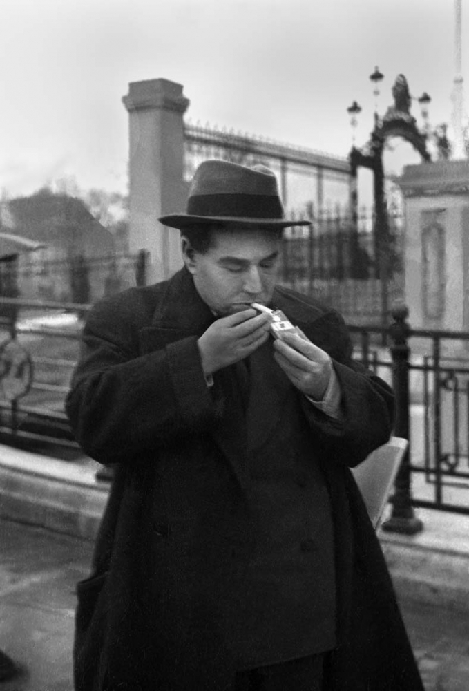 Schwarz-Weiß-Porträt von Egon Erwin Kisch, der sich auf der Straße eine Zigarette anzündet