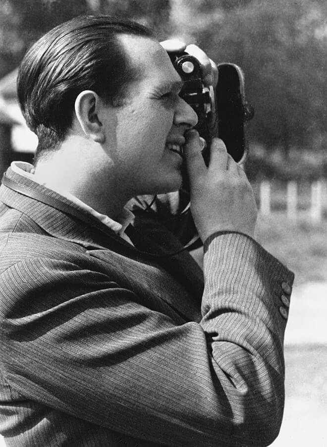 The photo shows Fred Stein in the side profile while photographing. He is wearing a pinstripe jacket and a shirt without a tie.