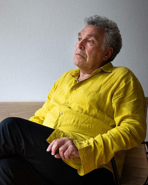 Photo of Frédéric Brenner in half profile, seated, wearing yellow shirt
