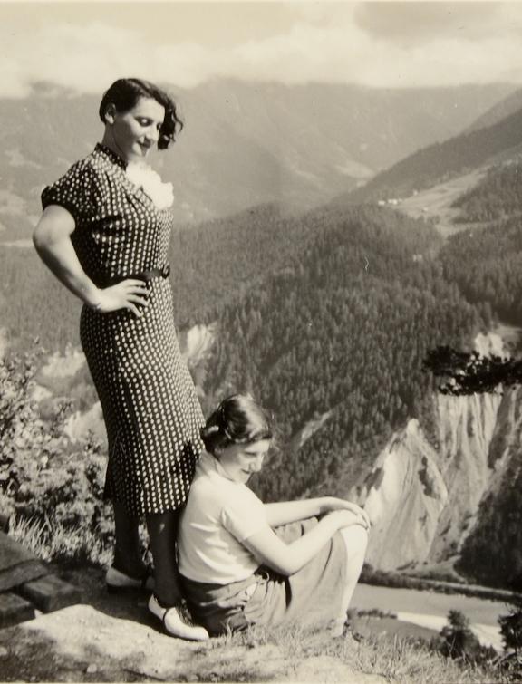 Eine Frau steht hinter ihrer Tochter, im Hintergrund ein Bergpanorama