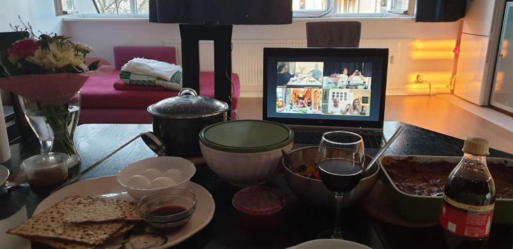 Auf einem gedeckten Tisch steht hinter den Nahrungsmitteln ein Laptop, in dem ein Video-Chat geöffnet ist.