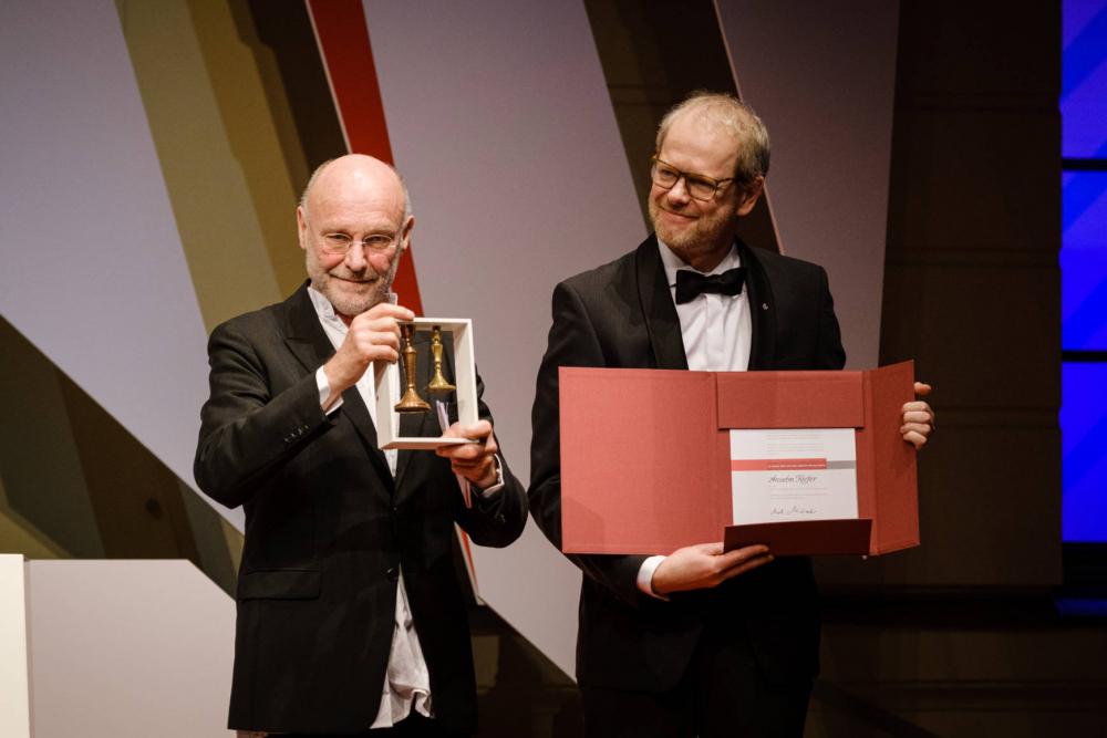 Zwei Männer halten Preis und Urkunde in die Kamera