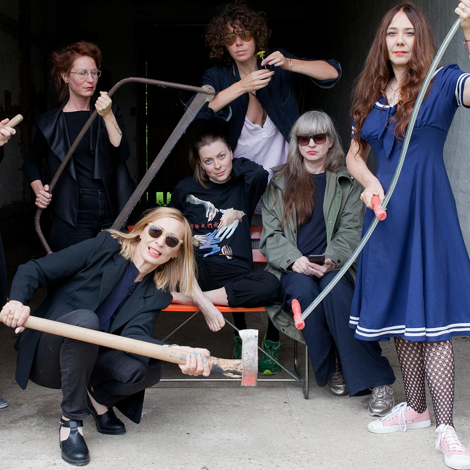 Gruppenfoto der Musikerinnen mit Axt, Sichel, Säge und Co.