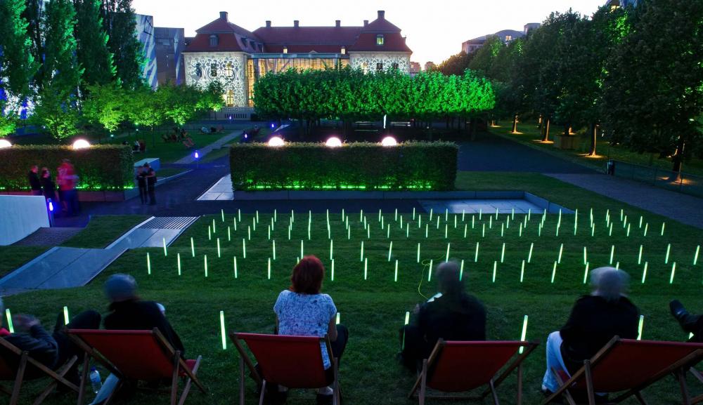 Menschen sitzen in roten Liegestühlen im Museumsgarten, der Garten ist unter dem Abendhimmel hell erleuchtet