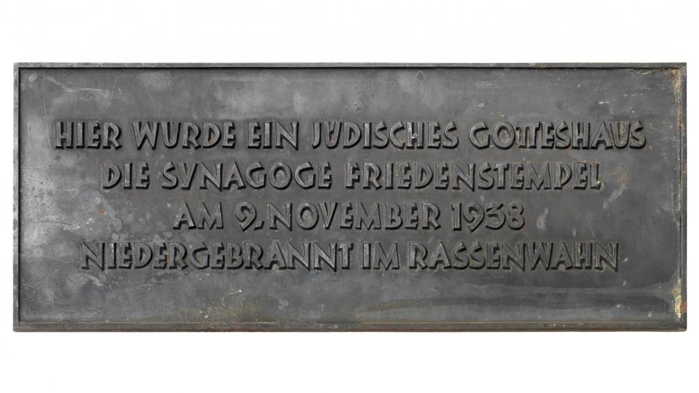 Eine Gedenktafel mit der Aufschrift »Hier wurde ein jüdisches Gotteshaus/ die Synagoge Friedenstempel/ am 9. November 1938/ niedergebrannt im Rassenwahn«