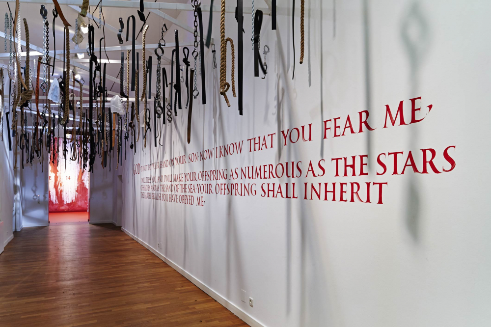 Multiple chains, handcuffs, and ropes hang from the ceiling, there is large red text written on the wall below it