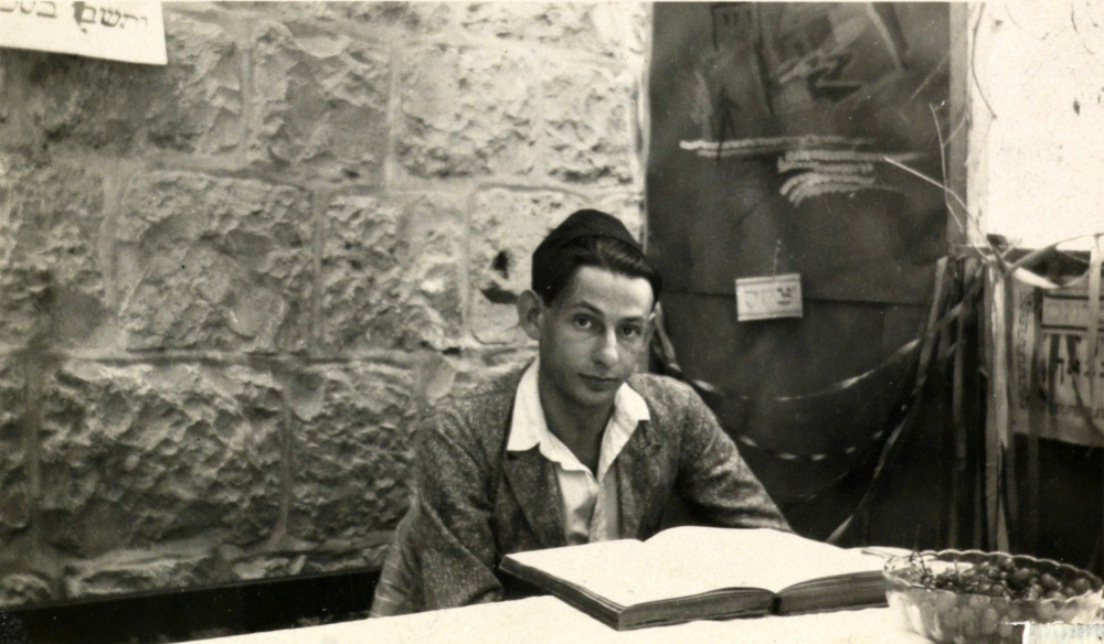 Black and white photography: a young man sits in front of an open book and looks into the camera.