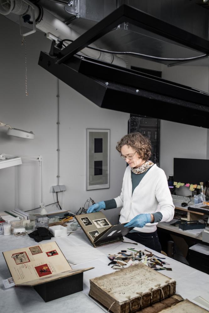Eine Frau mit blauen Gummihandschuhen steht an einem Arbeitstisch und schaut ein altes Fotoalbum durch.