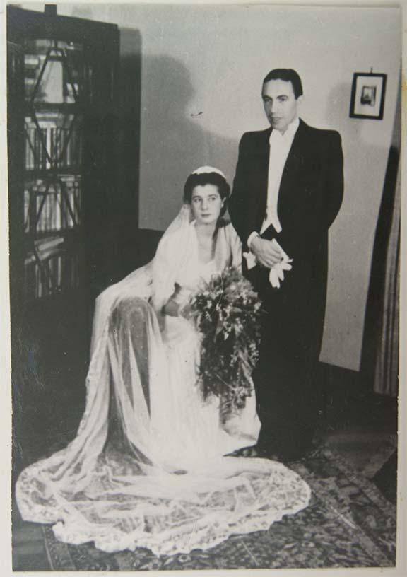 Schwarz-Weiß-Foto eines Brautpaars, sie sitzt, er steht rechts hinter ihr. Links im Bild ist ein Buffet zu sehen, der Raum wirkt wie ein Wohnzimmer
