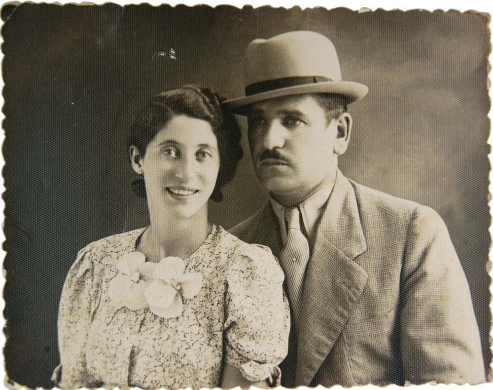 Double black-and-white photographic portrait showing Sally Katz smiling on the left in a floral-patterned dress and Heinrich Katz on the right in a suit and hat.