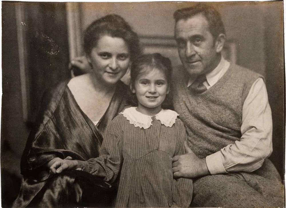 Familienfoto in schwarz-Weiß: Minni und Jakob Steinhardt sitzen, zwischen ihnen steht Josefa in einem karierten Kleid mit weißem Spitzenkragen. Minni Steinhardt trägt eine glänzende, dunkle Tunika; Jakob eine Wollweste mit Hemd und Krawatte