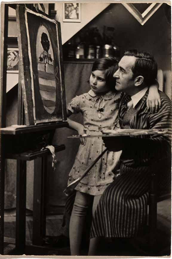 Ein Mann mit Pinsel und Palette in einer Hand kniet vor einer Staffelei. Im anderen Arm hält er ein Mädchen, beide schauen auf das Bild, an dem er gerade zu arbeiten scheint