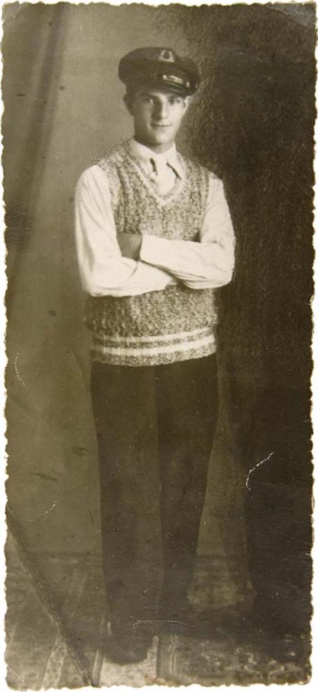 Porträt eines stehenden jungen Mannes, der eine Matrosenmütze und einen handgestrickten Pullunder trägt. Er schaut freundlich in die Kamera und wirkt sehr zerbrechlich