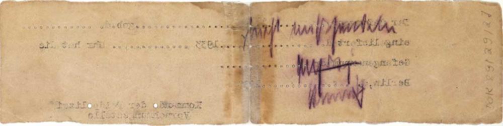 Rückseite eines vergilbten Zettels in extremem Querformat. Einige Buchstaben des Schreibmaschinentextes der Vorderseite sind als spiegelverkehrter Abdruck sichtbar, außerdem eine handschriftliche Notiz