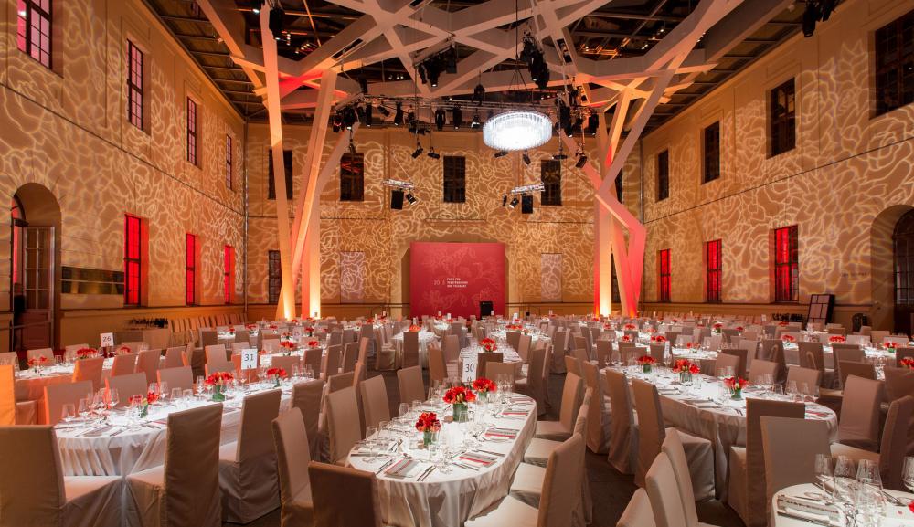 Der Glashof ist mit roten und weißen Lichtern beleuchtet, große, mit roten Blumen, Silberbesteck und Weingläsern geschmückte Esstische füllen den Innenhof.