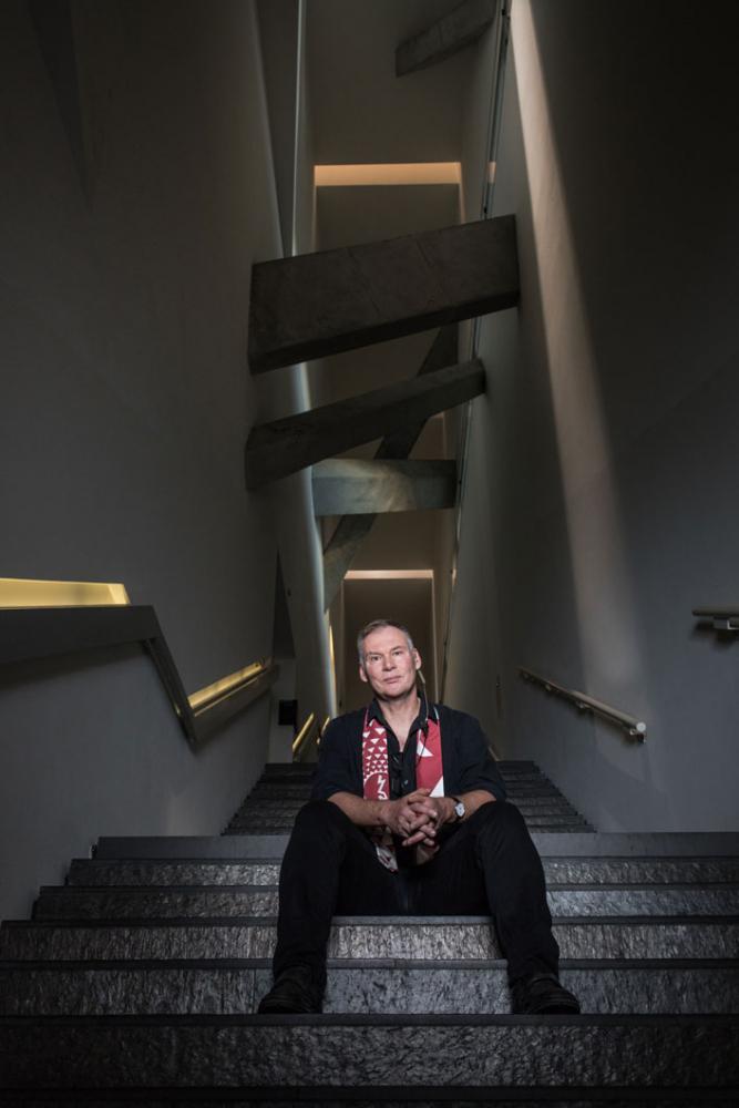 Ein Mann mittleren Alters sitzt auf der Sackler-Treppe im Jüdischen Museum Berlin