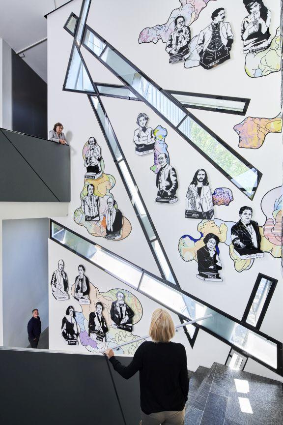 Wand, die von schmalen, länglichen Fensterbändern durchzogen ist, die sich teilweise kreuzen. Dazwischen hängen gezeichnete bunte Porträts.