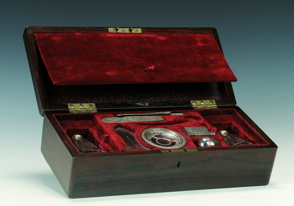 Opened black box with red velvet material filled with silver objects