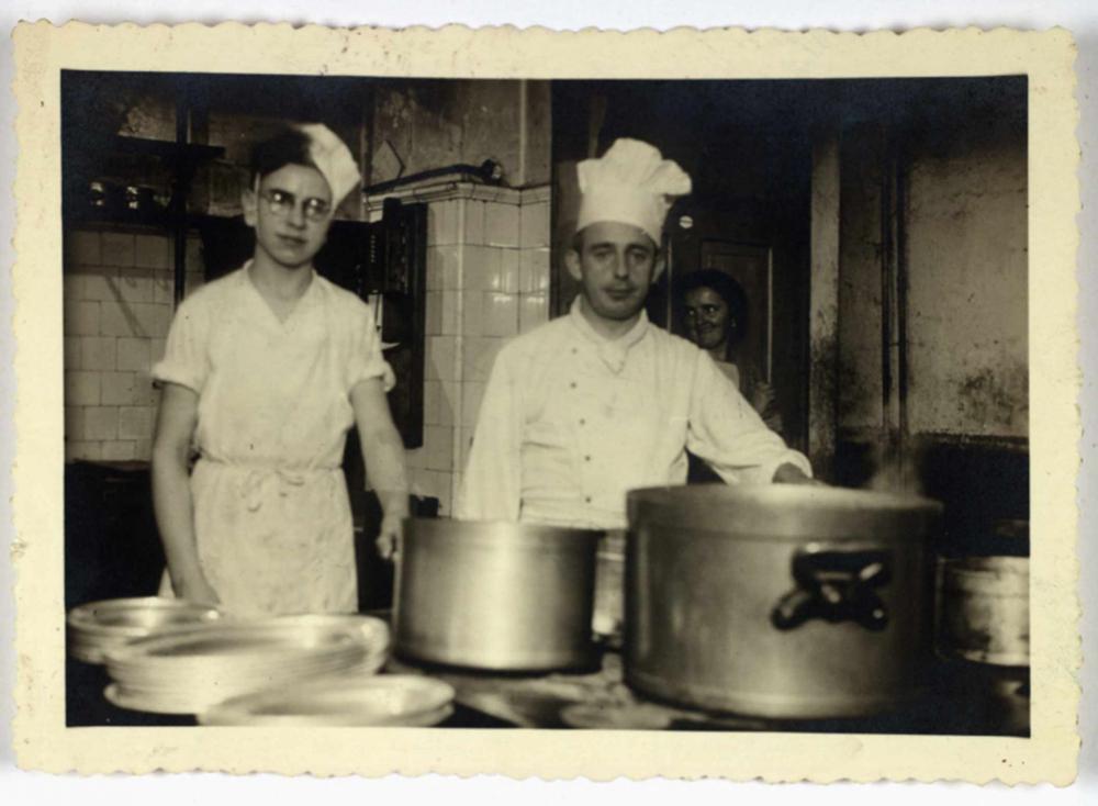 Henry Wuga mit Kochlehrlingsmütze in der Hotelküche, neben ihm ein Koch, im Hintergrund eine weibliche Küchenhilfe