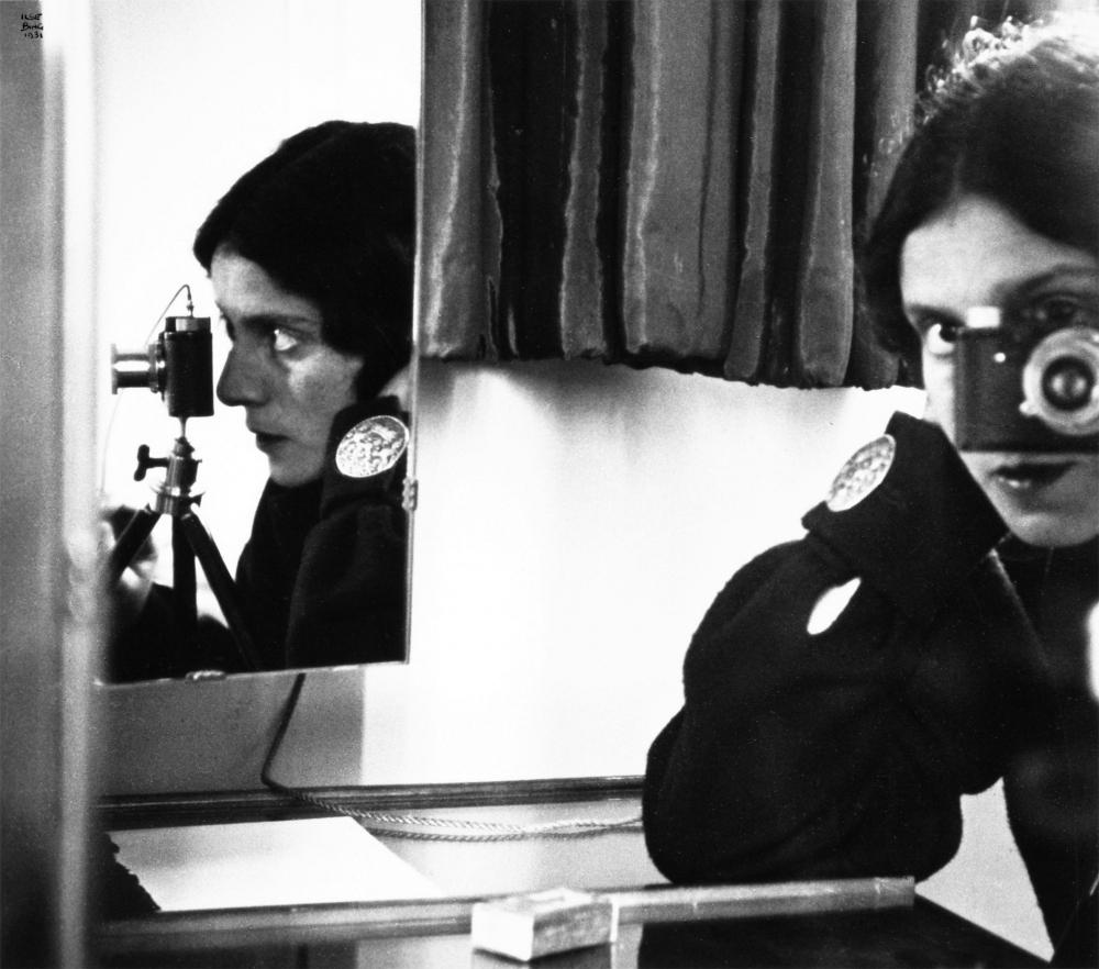 Schwarz-Weiß-Fotografie einer Frau, die durch eine Kamera sieht, ein Spiegel zeigt sie zusätzlich im Profil