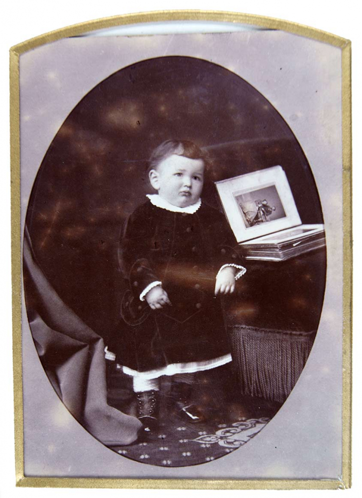 Black-and-white photo of a standing baby alongside an open photo album