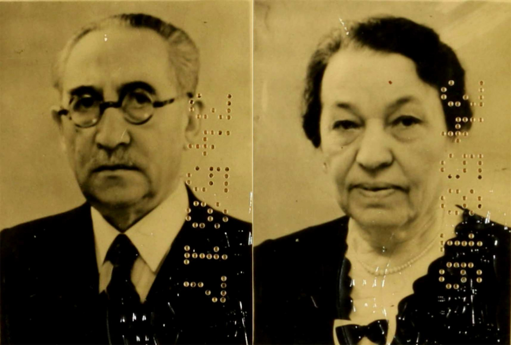 Passport photo of an older man wearing glasses and a suit and necktie together with an older woman with a ribboned blouse and a necklace; the photos bear numeric codes