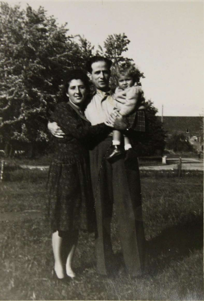Black-and-white photograph of a family taken outdoors; the father is holding his one-year-old daughter in his arms