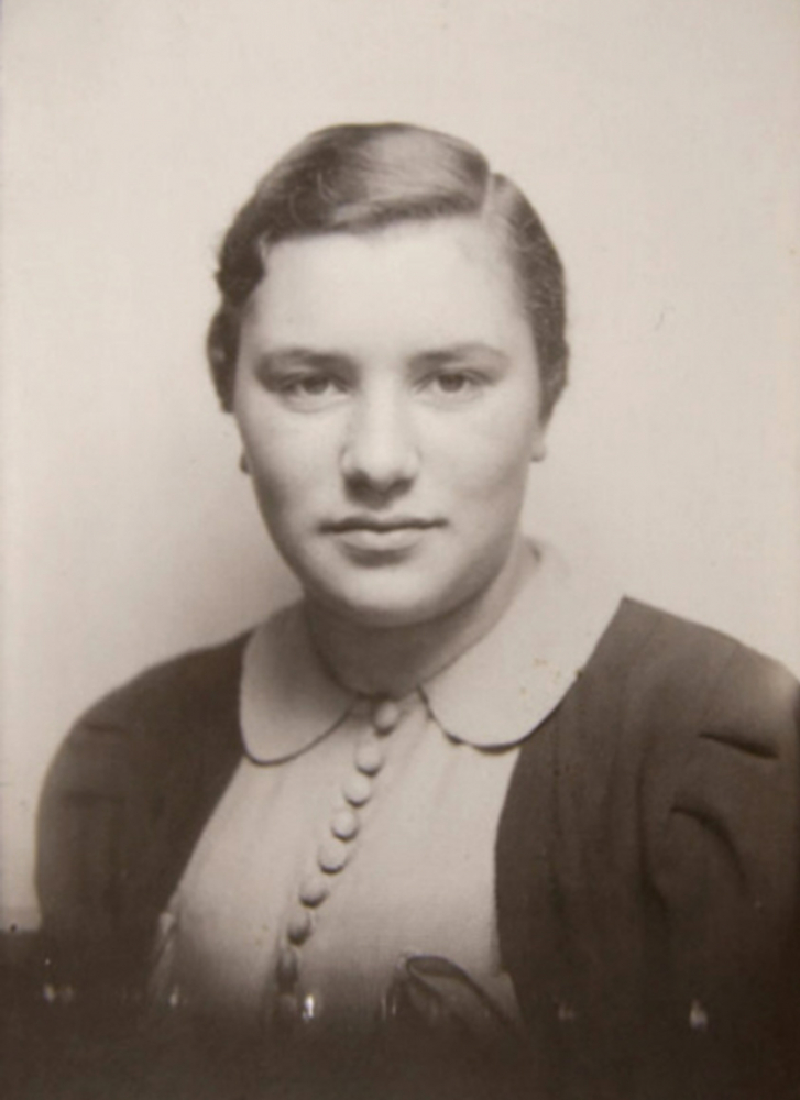 Black-and-white photograph of a young woman in a blouse and a cardigan