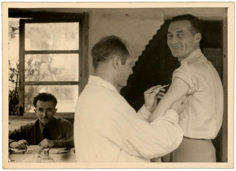 Black-and-white photograph of a man holding a scalpel to the upper arm of another man who is smiling for the camera