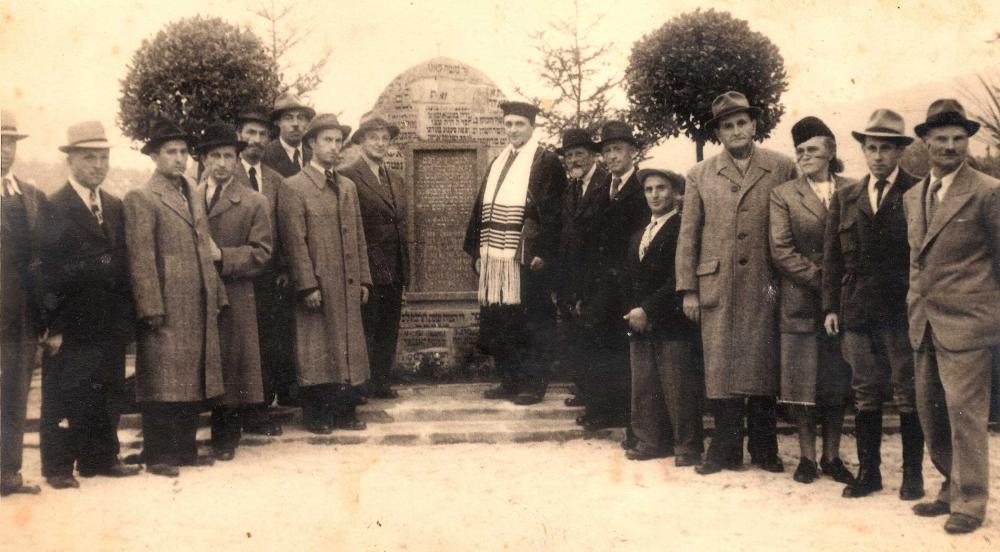 An einem Gedenkstein Spalier stehende Menschen mit Hut, in der Mehrzahl Männer