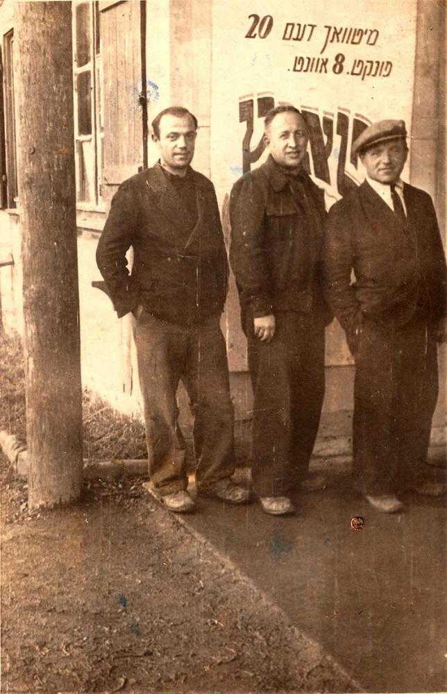 Schwarz-Weiß-Foto dreier Männer, leicht seitlich stehend, die Hände in den Taschen