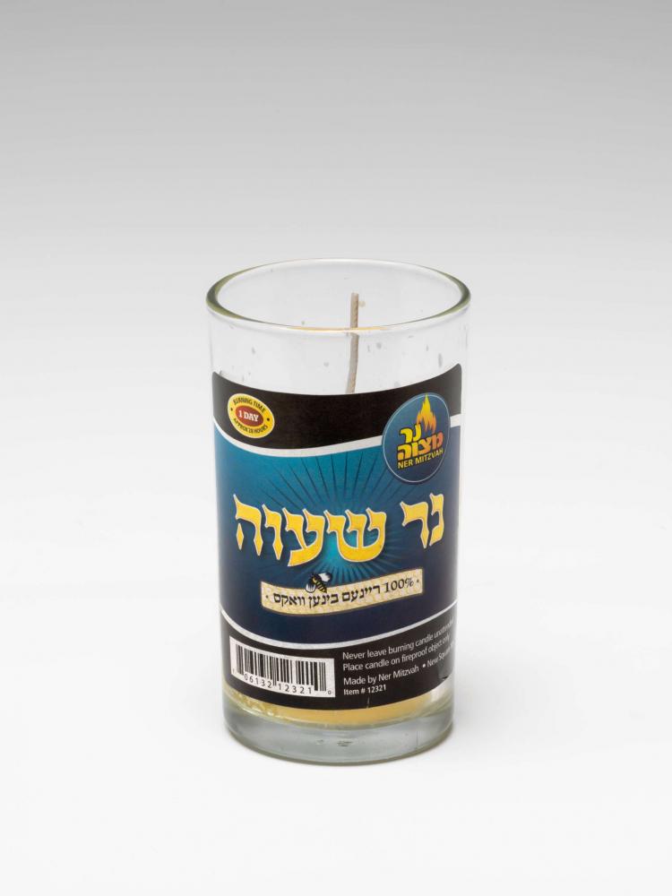 Ein Kerze im Glas mit hebräischer Beschriftung