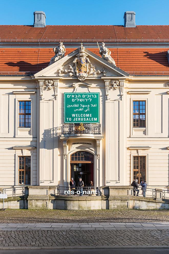 Auf dem Farbfoto ist die Fassade des Jüdischen Musuems Berlin mit dem einem Verkehrsschild nachempfundenen Schild mit der Aufschrift Welcome to Jerusalem in den Spachen Englisch, Arabisch und Hebräisch zu sehen.