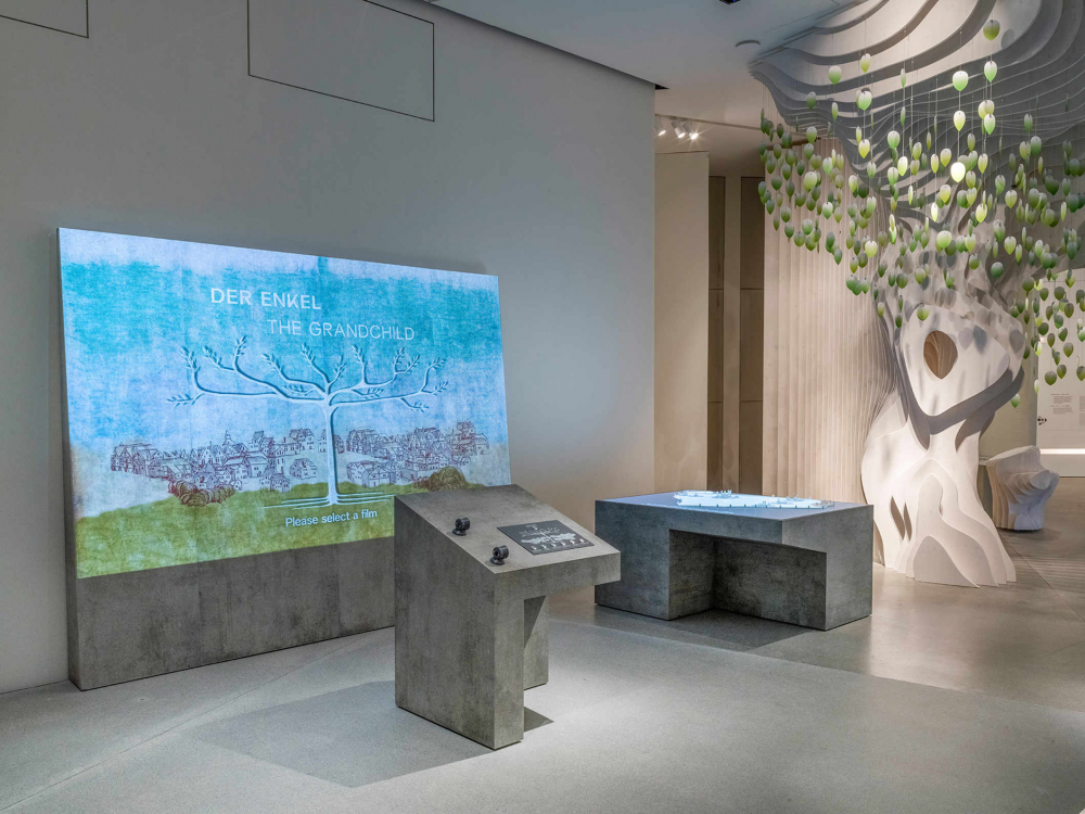 Exhibition space with concrete exhibition furniture, a projection of a tree, around which a green meadow and houses stand
