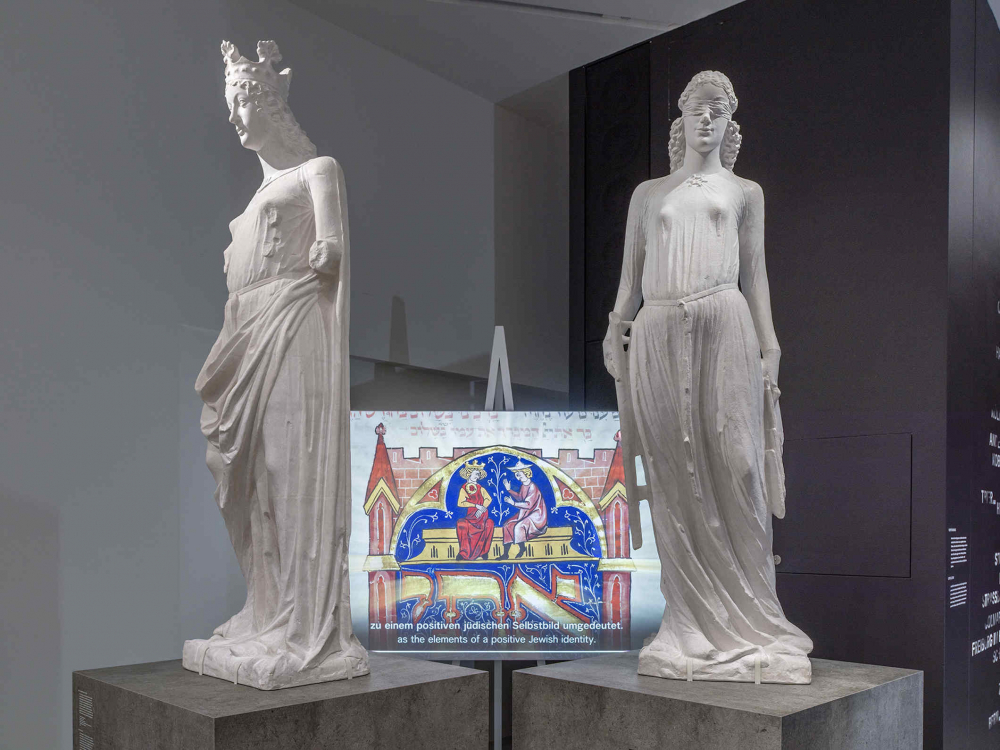 Two white sculptures, in the background a screen on which a film is running