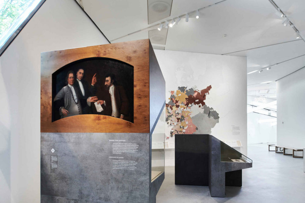 Showcases made of concrete and wood, in them a painting with three persons in the background a map of the territory of present-day Germany