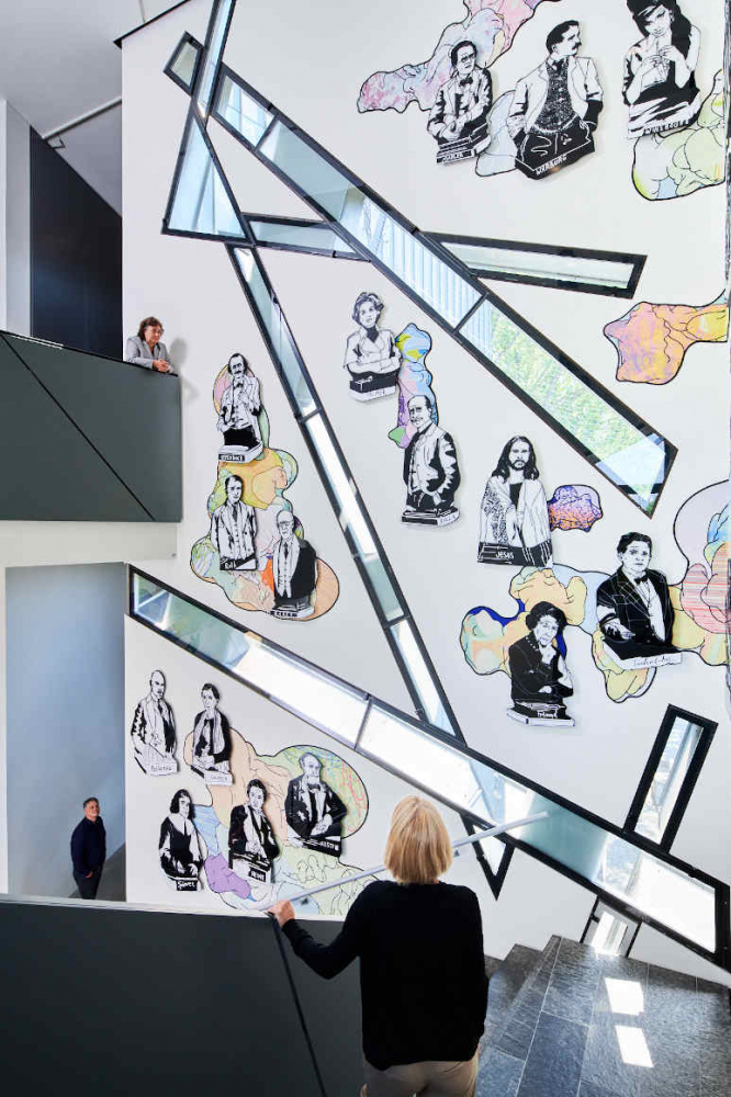 Stairs with people and with illustrations of people on the wall