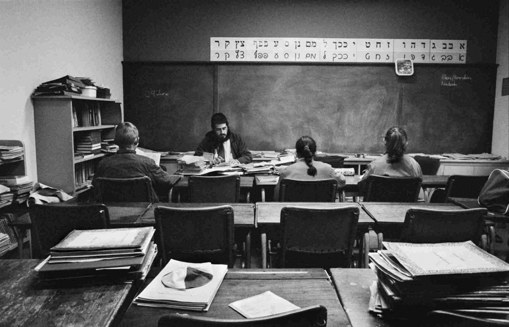 Black and white photograph of a classroom, back view of two students, in front of them a teacher, above the blackboard the Hebrew alphabet
