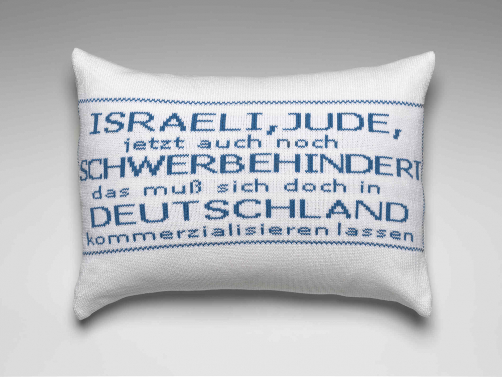 White pillow with embroidered blue text