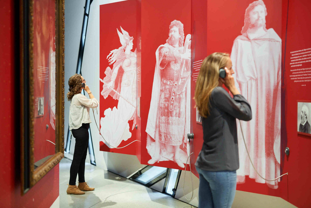 Two visitors stand with listeners in their hands in front of a red wall with white figures