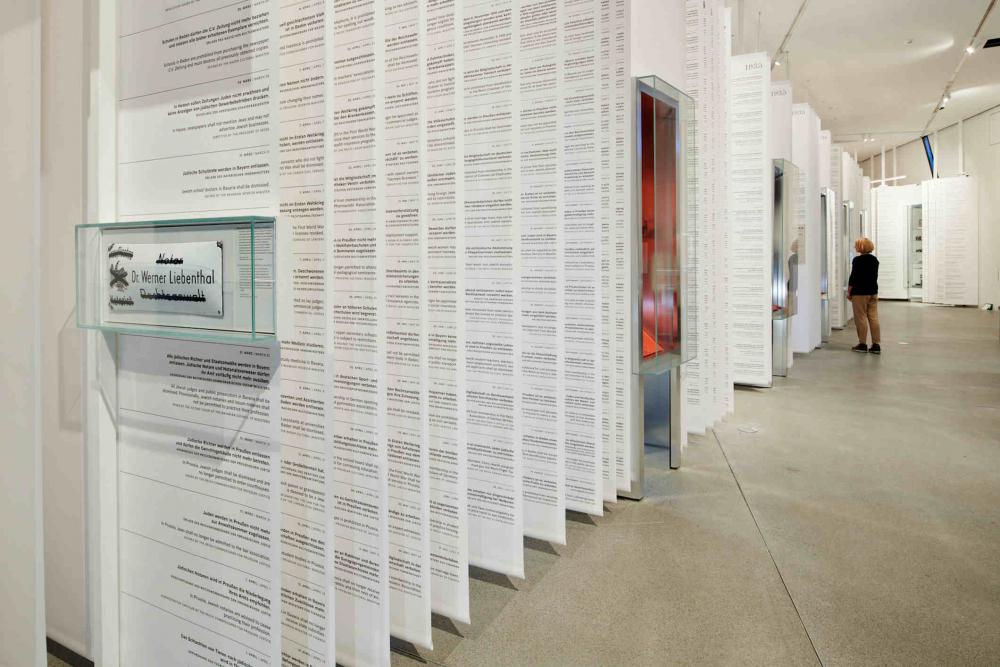 Lange weiße Papierbanner mit Text hängen von der Decke unterbrochen von Vitrinen, im Hintergrund steht eine blonde Frau