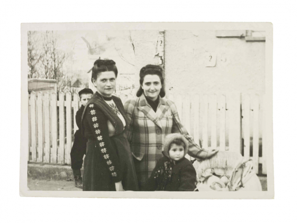 Photo of two women and two children in front of a picket fence