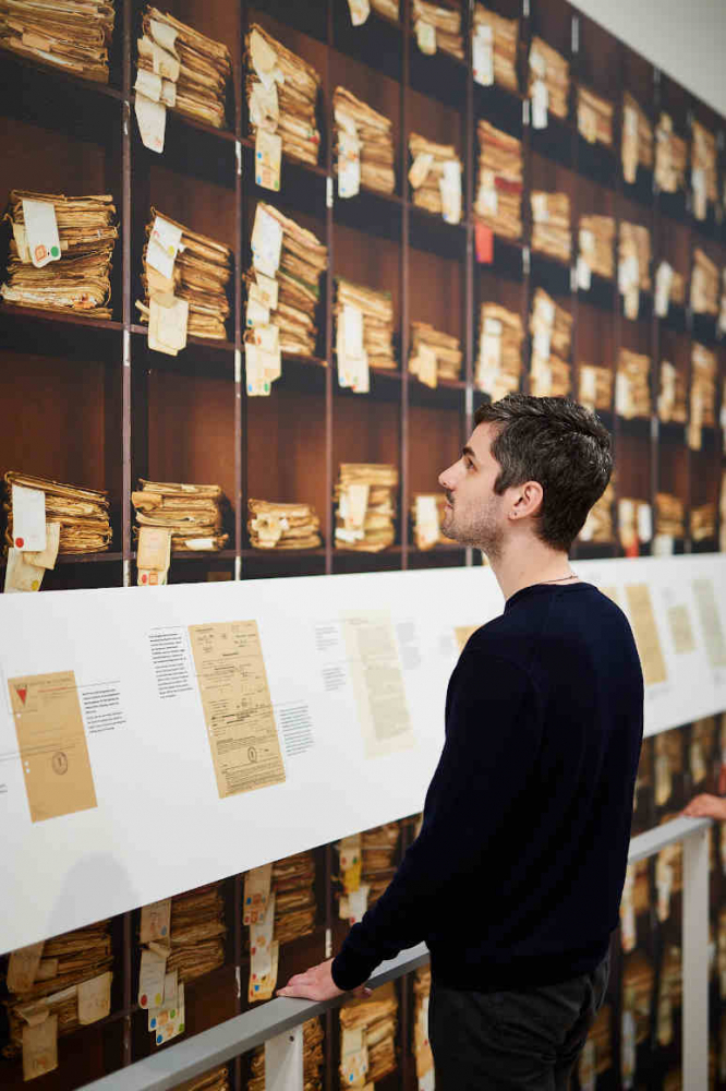 Man stands in front of a wall with a photo of a shelf with many old files