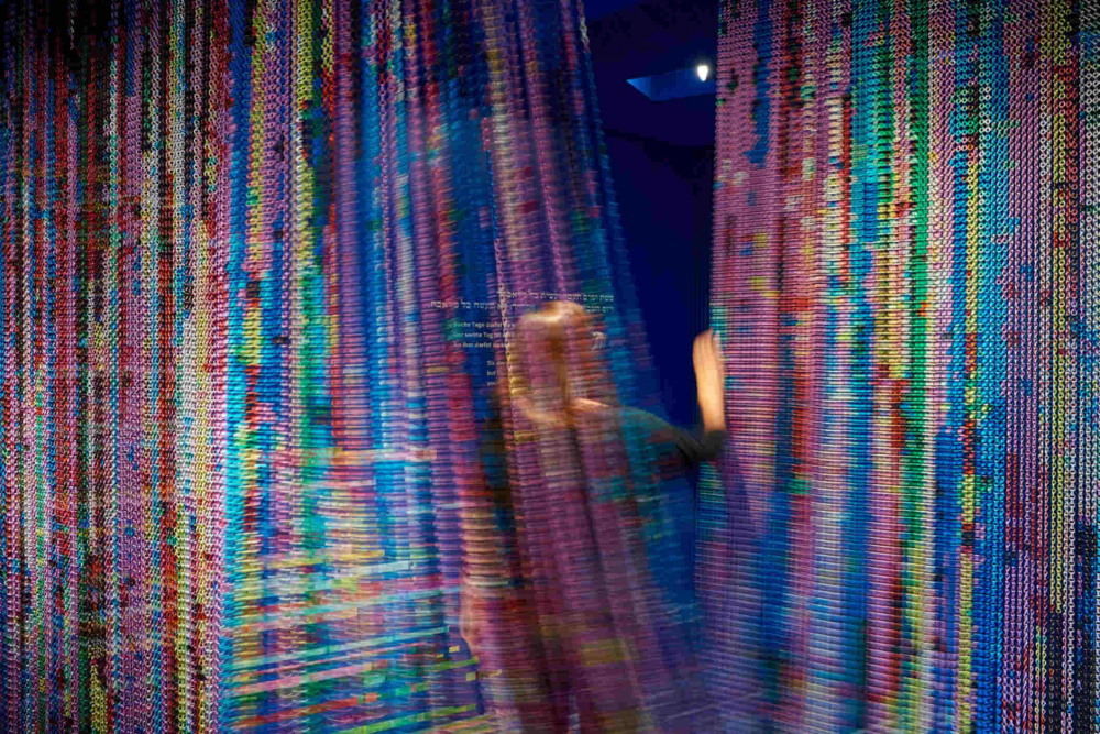 Colorful curtain in motion through which a person passes