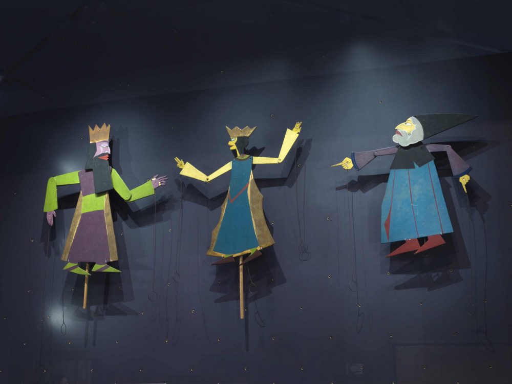 Three figures each attached to a stick, two with a crown, one with a pointed hat